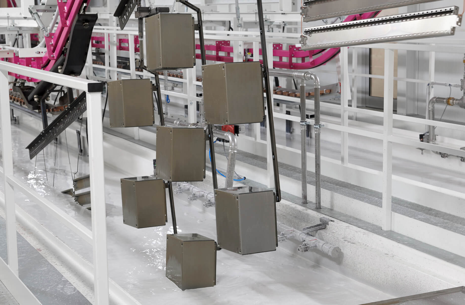 The manufactured enclosures are mounted on special fixtures before being immersed in the primer that will protect them from corrosion. The indestructible outer skin is then finished with a powder coating.